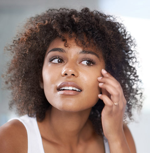 Black woman with curly hair who appears to be looking in the mirror rubbing something into her face.