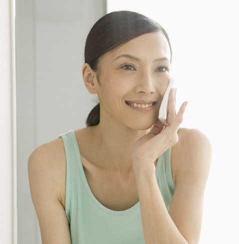 Asian woman in green tank top smiling, and rubbing her face with a towelette.