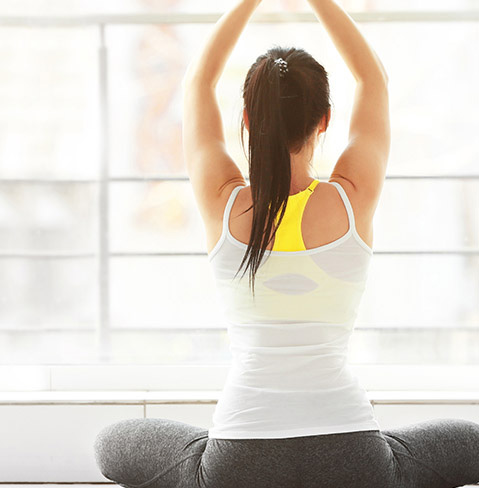 Back of a woman with dark hair, wearing a white tank top and a yellow sports bra with her arms raised.